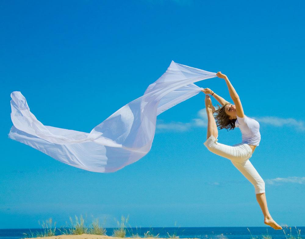 海边跳跃的外国美女摄影图片